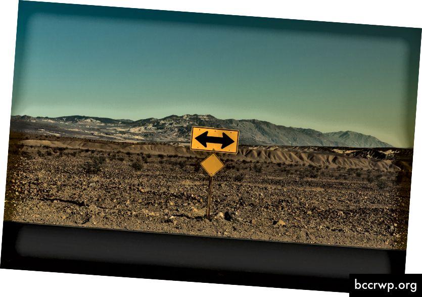 """Pablo García Saldaña """"Kollane liiklusmärk musta noolega, mis näitab mõlemat suunda Kuival oru lähedal kuival tee ääres"""", autor Pablo García Saldaña saidil Unsplash"""