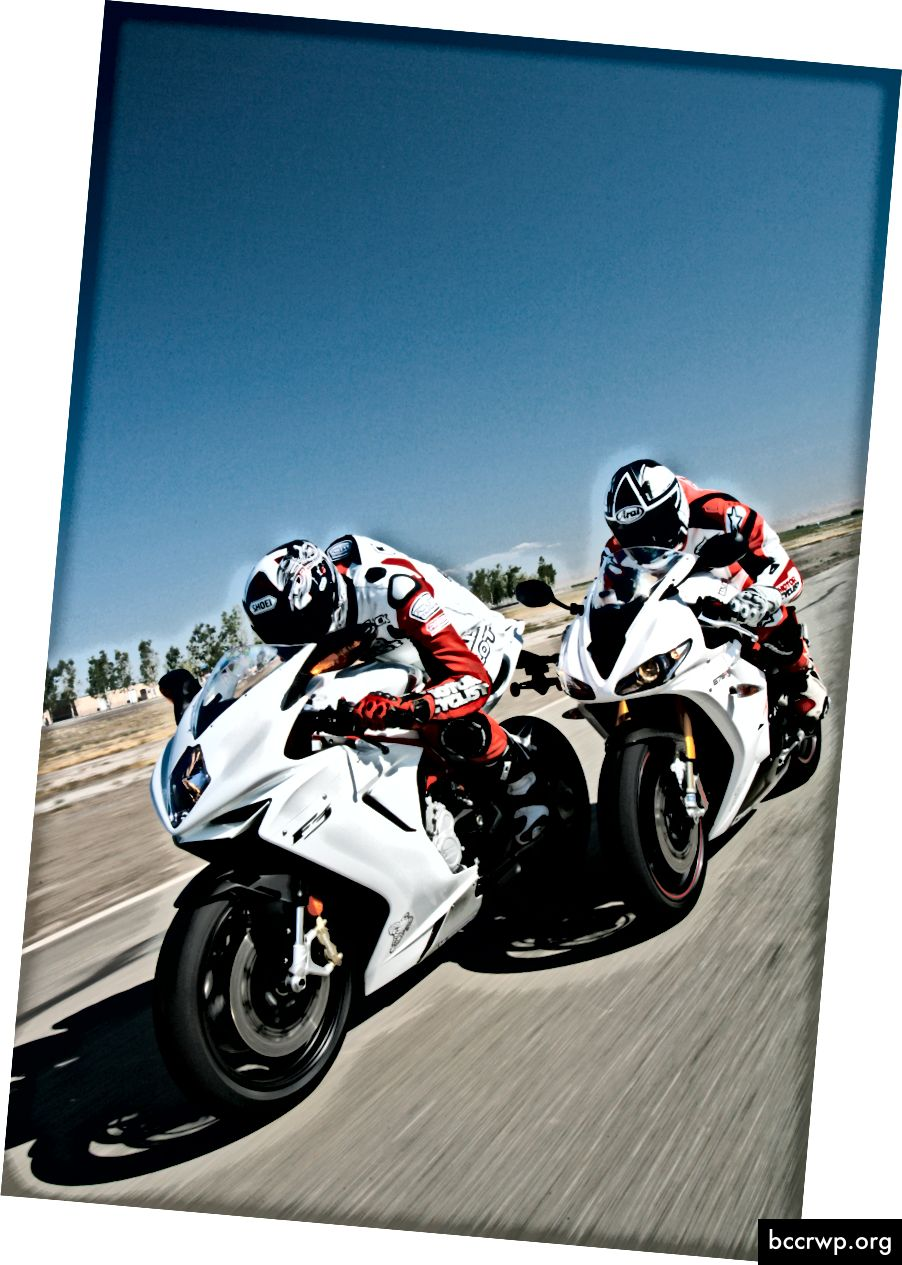 """""""Du žmonės susidūrė su šalmais ant baltų motociklų, lenktyniaudami takeliu po žydru dangumi"""", autorius Joe Neric svetainėje """"Unsplash"""""""