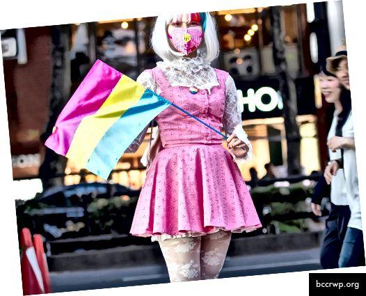 Mynd: ein manneskja sem heldur fastan fámennsku fyrir hátíðarstol og klæddist hátíðarprís við prúðgönguna í Pride Tokyo.