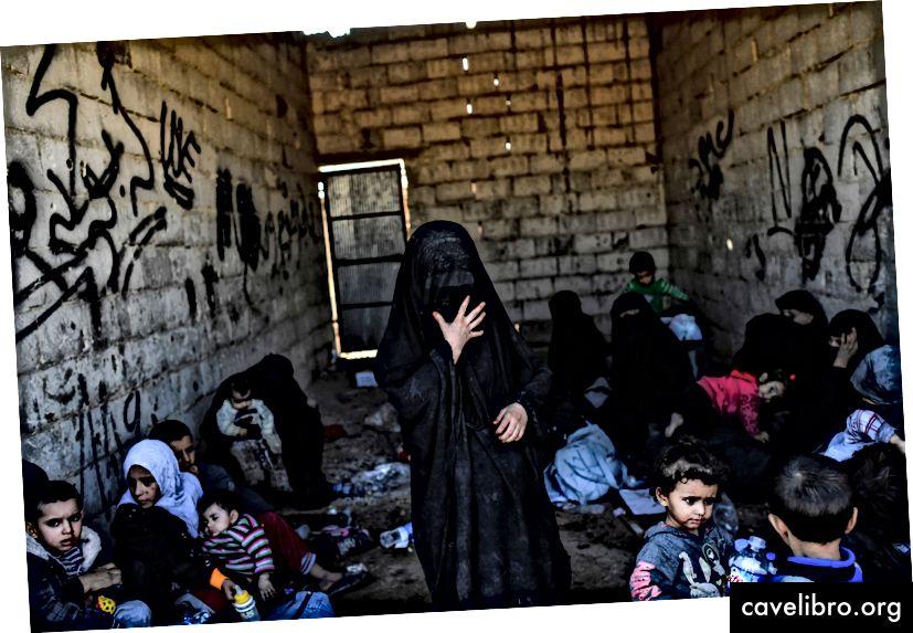 Sýrske ženy a deti sa zhromažďujú na západnom fronte po úteku z centra mesta Raqqa 12. októbra 2017. Sýrske demokratické sily (SDF), sýrske bojovníci podporované americkými špeciálnymi silami, bojujú o očistenie posledných zostávajúcich džihádistov zdrvujúcich sa v rozpadajúcej sa pevnosti. z Raqqa. (BULENT KILIC / AFP / Getty Images)