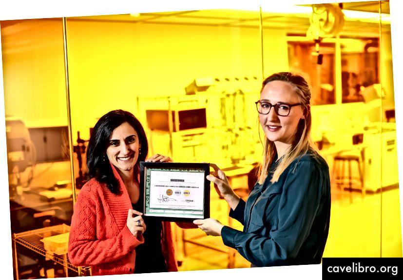 (D) Jennifer Ballew, coordinatrice du programme GreenLabs / LEAC au MIT, présente le groupe de recherche Conformable Decoder, PI Canan Dagdeviren (L), avec le Green Lab Certificate pour l'espace laboratoire du groupe.