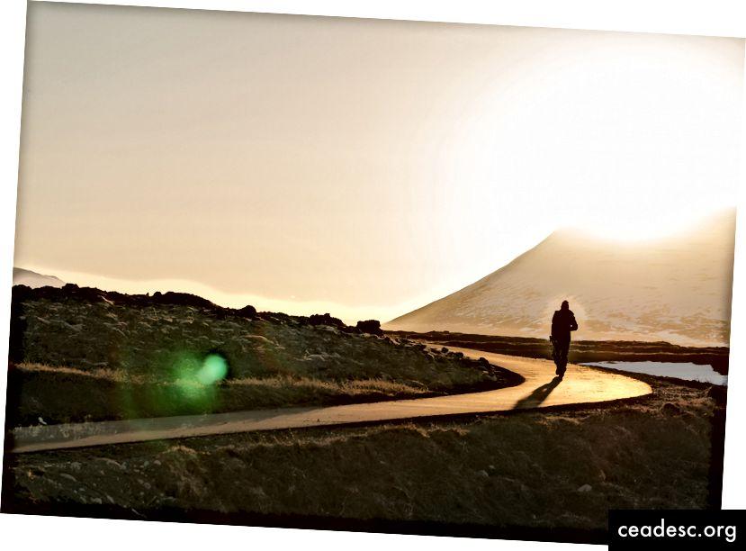 """""""Inimese siluett, kes Góðafossis päikeseloojangu ajal radadel kõnnib"""", autor Mahkeo saidil Unsplash"""