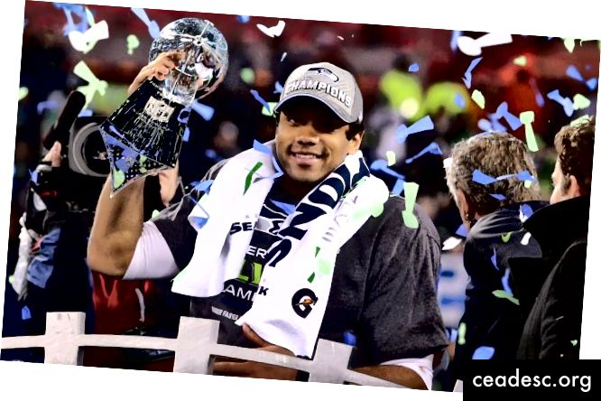 NFL tysiącletni rozgrywający Russell Wilson z Super Bowl Trophy w ręku.