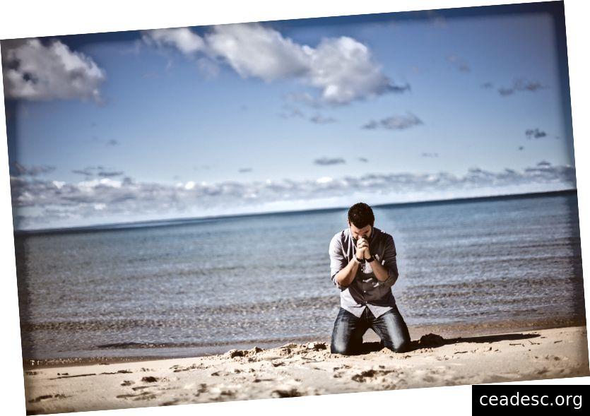 """""""Un homme en chemise et jeans agenouillés au bord d'une plage, les mains jointes au menton"""" par Ben White sur Unsplash"""