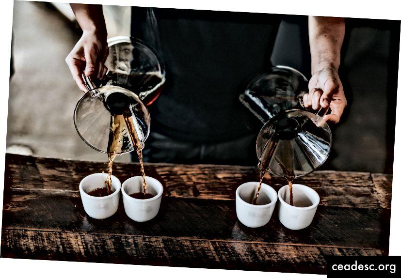 """""""Un barista versant du café dans quatre tasses à la fois"""" par Nathan Dumlao sur Unsplash"""