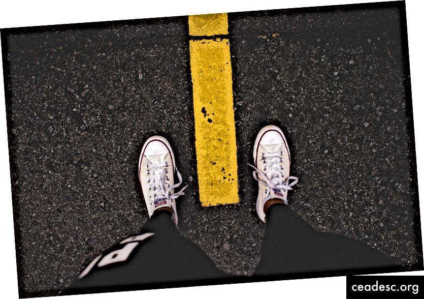 Một người đàn ông nhìn chằm chằm vào đôi giày của mình, mỗi người ở một bên của đường phố màu vàng, bởi Nadine Shaabana trên.