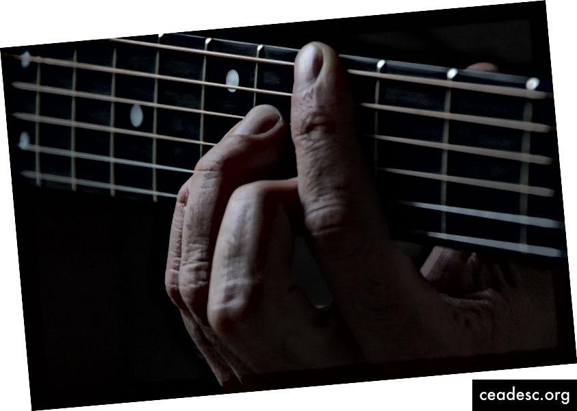 Cận cảnh một người gần gũi với một người đàn ông Tay trên cổ cây đàn guitar của Scott Gruber trên.