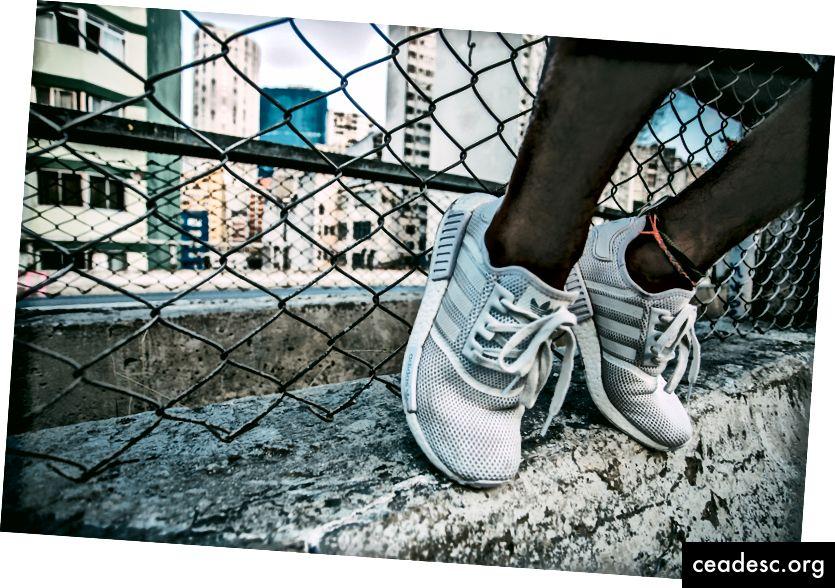 """Praktika daro tobulą. Ant grandininės tvoros sportininkas ilsisi baltais """"Adidas"""" batais. Kreditas: """"Unsplash"""""""