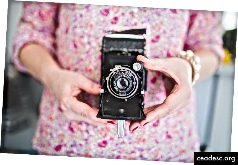 """Sakyk sūris! Moteris rausvuose gėlių marškiniuose, laikančiuose retro """"Nikon"""" fotoaparatą. Kreditas: """"Unsplash"""""""