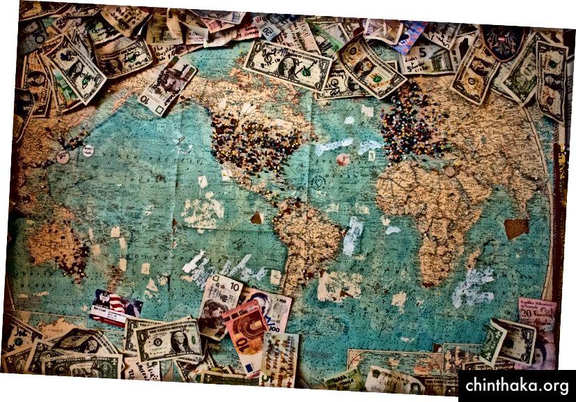 """""""Verschiedene Geldscheine, die an verschiedenen Orten auf einer großen Weltkarte mit bunten Stecknadeln befestigt sind"""" von Christine Royon Unsplash"""