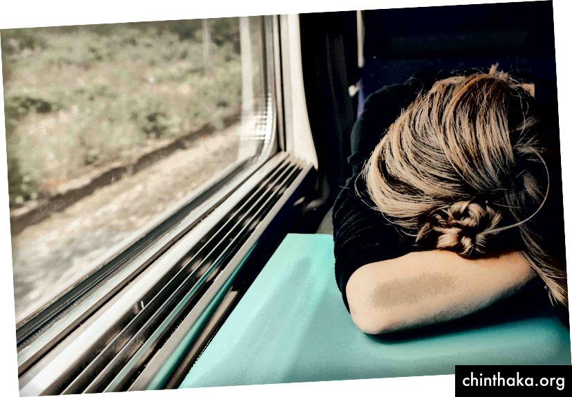 UnsplashのAbbie Bernetによる「電車のトレイテーブルに頭を下げた疲れた女性」
