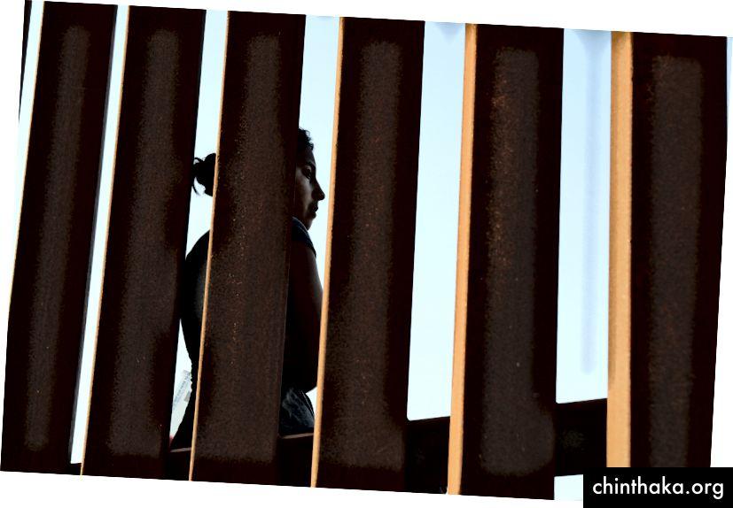 مهاجر من أمريكا الوسطى يقف عند السياج الحدودي بين الولايات المتحدة والمكسيك بعد عبوره إلى تكساس في 12 يونيو 2018. الصورة: جون مور / غيتي إيمدجز