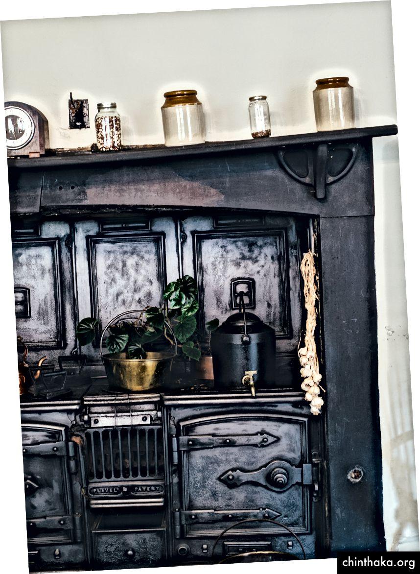"""""""Ein altes schwarzes Küchenregal mit Herd, Topfpflanze, Gläsern, Wasserkocher und Uhr."""" Von Annie Spratt auf Unsplash"""