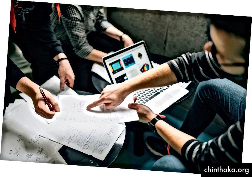 """""""Sekelompok orang melakukan brainstorming atas laptop dan lembaran kertas"""" oleh Štefan Štefančík di Unsplash"""