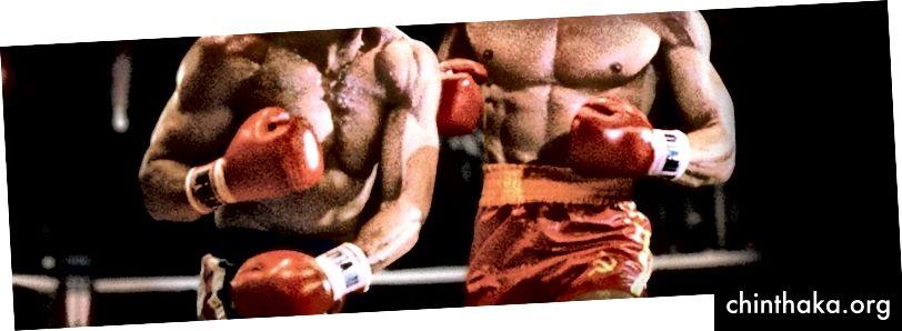 Slika boksačkog meča dvojice muških boraca. Lica su im izvan okvira. Borac s lijeve strane otpustio je lijevu udicu borcu u desnoj. Borac s desne strane nosi crveni kratki s malim simbolom Sovjetskog Saveza.