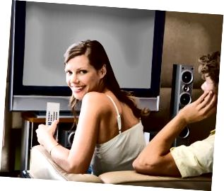Pareja mirando TV LCD con altavoces de sonido envolvente