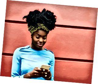 Kobieta używa mądrze telefon przed ścianą