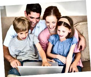 充满爱的家庭一起在沙发上使用笔记本电脑