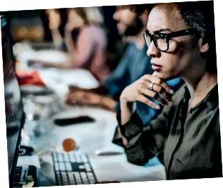 Koncentrerad afroamerikansk kvinna brainstorming medan du kodar data på stationär PC.