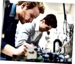 ইলেকট্রনিক্স উপাদানগুলিতে কাজ করছেন দুই তরুণ সুদর্শন প্রকৌশলী