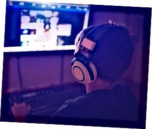 Kleiner Junge mit Headset unter Verwendung des Computers