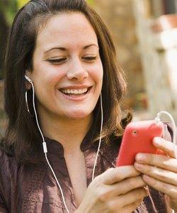Kvinde, der lytter til musik på en mobiltelefon