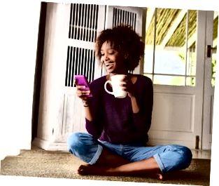 Le kvinnan som hemma sitter på golvet med mobiltelefonen