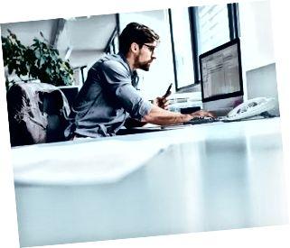 Ung forretningsmand på kontoret, der arbejder på computeren