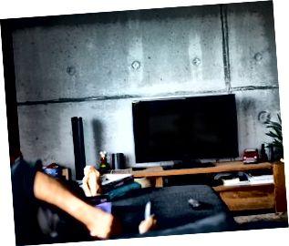Zadný pohľad na muža, ktorý sleduje televíziu v obývacej izbe
