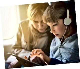 Mädchen mit Mutter, die im Zug reist und auf Tablette spielt