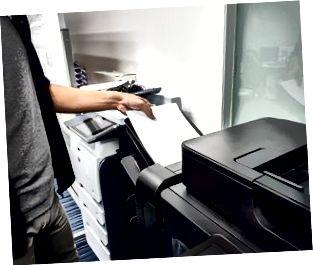 affärsman satte pappersark i skrivarfacket för att skriva ut dokument