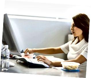 Ung forretningskvinde spiser frokost ved skrivebordet