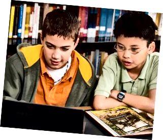Drenge, der bruger laptop i biblioteket