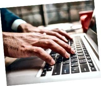 Öppnad bärbar dator och manlig maskinskrivning