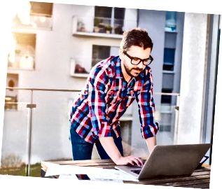 นักธุรกิจทำงานจากที่บ้านด้วยแล็ปท็อปยืนอยู่ที่ระเบียง