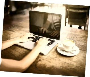 একটি ক্যাফেতে একটি ল্যাপটপ কীবোর্ডে বালিকা টাইপ করছে