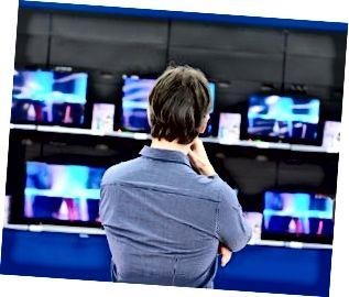 El hombre mira televisores LCD en la tienda