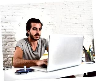 hipster student eller affärsman som arbetar med bärbar dator på kontoret