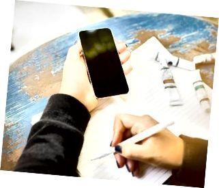 flicka skriver i anteckningsboken, med mobiltelefon och bläckritning