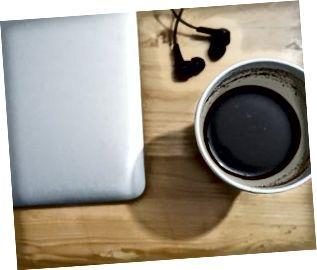 Kop sort kaffe og MacBook på bordet