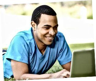 Ung man som använder bärbara datorn utomhus