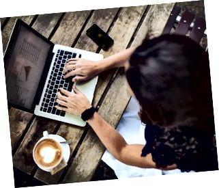 Kvinna som använder hennes bärbara dator på ett kafé