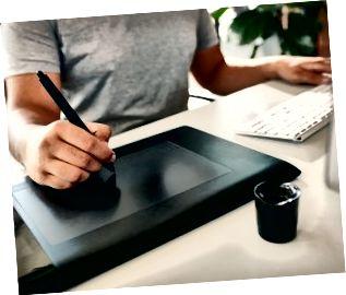 Grafisk designer som använder den digitala minnestavlan och datorn på kontoret