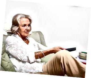 Äldre kvinna som använder fjärrkontrollen medan du kopplar av på fåtöljen hemma