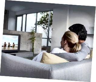 Par som kopplar av på soffan som håller ögonen på tv, bakre sikt