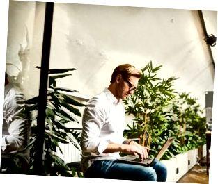 Giovane imprenditore maschio alla moda occupato con stoppia che si siede nell'ufficio dello spazio aperto e che utilizza computer portatile mentre sviluppando affare online