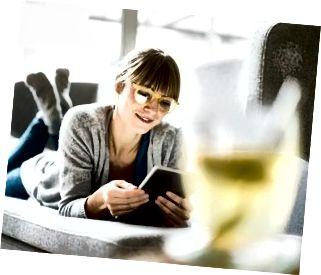 Lächelnde Frau, die auf Couch mit Tablette liegt