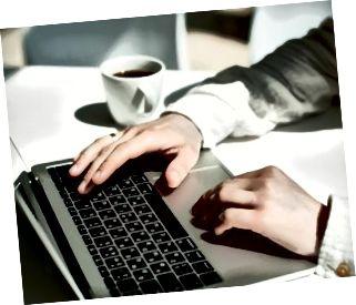 Computer portatile funzionante dell'uomo d'affari per il nuovo progetto architettonico. Notebook dal design generico sul tavolo. Giovane uomo d'affari che lavora con il computer portatile all'ufficio. Uomo irriconoscibile utilizzando un moderno computer portatile