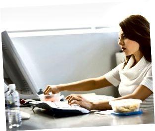 Junge Geschäftsfrau, die Mittagessen am Schreibtisch isst