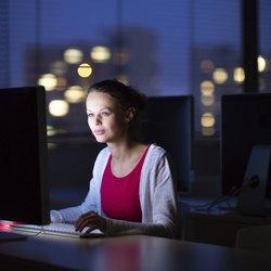 Hübsche, junge Studentin mit einem Desktop-Computer / PC